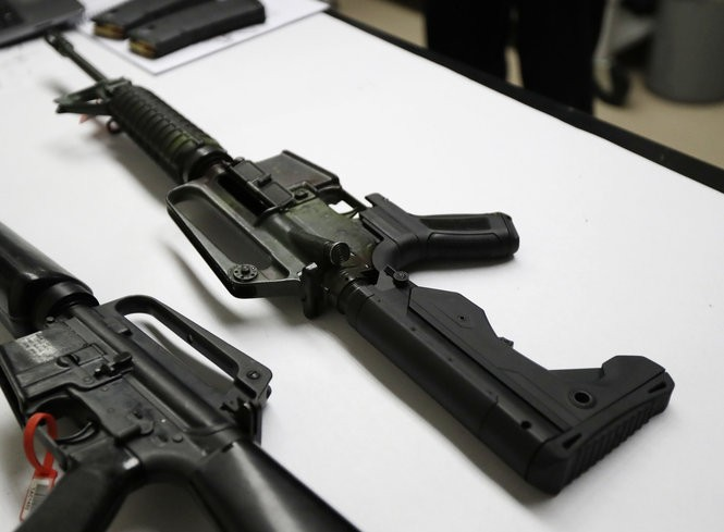 The semi-automatic rifle at right has been fitted with a so-called bump stock device to make it fire faster. It sits on a table at the Washington State Patrol crime laboratory in Seattle.