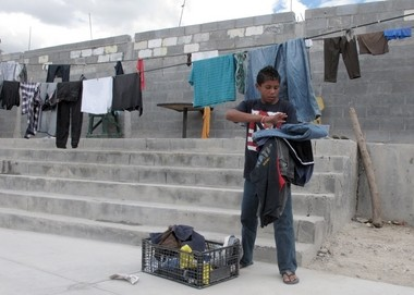 Brian Duran, 14, of Comayagua, Honduras, collects his line-dried laundry at a migrant shelter in Reynosa, Mexico, on Monday. He traveled alone to the U.S.-Mexico border in hopes of getting across.