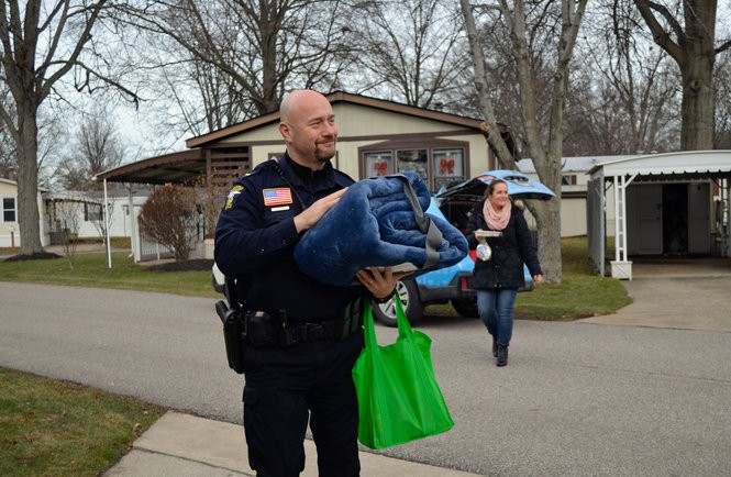 Olmsted Township Police Lt. Mark Adam carries a blanket and extra food as he and Wendi Schwartz, executive director, deliver emergency kits to clients who receive their weekly Meals on Wheels. These emergency kits were in partnership with Subaru's Share the Love campaign.