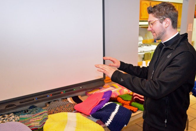 Rev. Ryan Cubera with St. Mary of the Falls Church blesses the shawls prior to their delivery to recipients.