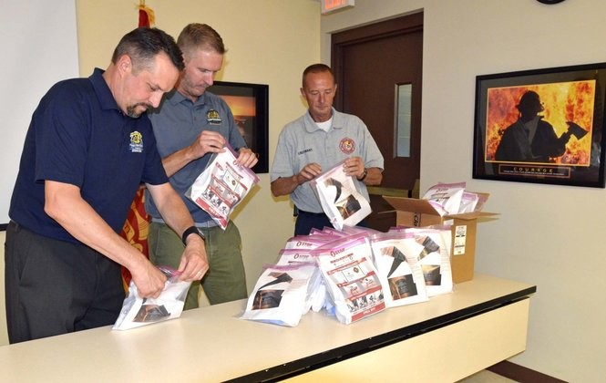 Olmsted Falls Schools Superintendent Jim Lloyd, Olmsted Falls Schools Transportation Supervisor Heath Krakowiak and Olmsted Township Fire Lt. Joe Fudale close the clasp on each kit prior to distribution.