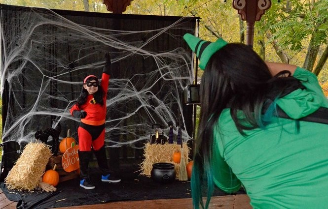 """Elaina Faust, 8, shows her enthusiasm as Violet of """"The Incredibles."""" while Paige Riggle of Paige Mireles Photography snaps a photo during Fall-O-Ween. Paige often donates her services to the community."""
