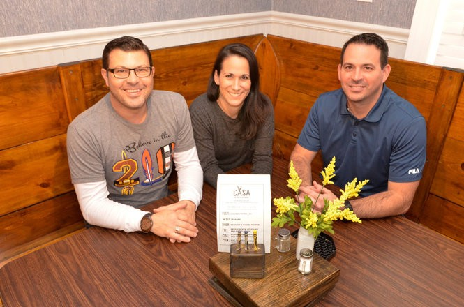 Owners Jason Salupo, left, his wife, Michelle, and her brother Mark Santarelli sit in the corner booth that accommodates several patrons.