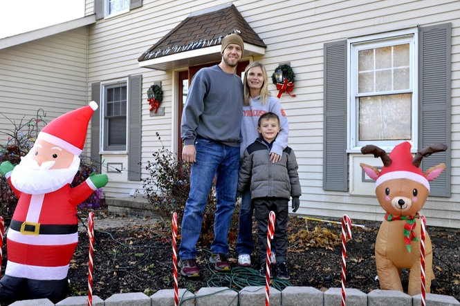 Shawn, Natasha and Lukas Carrigan take five during their yard decorating on Oakridge Drive in Olmsted Township.