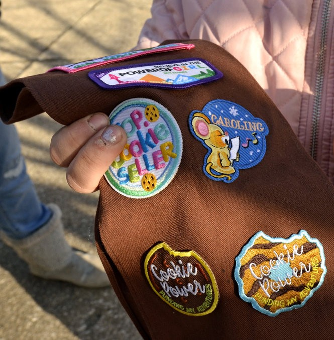 Isabella Wacker shows the Girl Scout badge she earned last year for caroling with her troop in Olmsted Township.