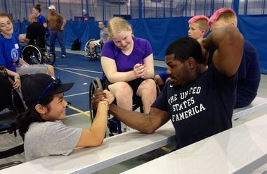 Cleveland native Dartanyon Crockett, a 2012 Paralympic silver medalist, arm wrestles Mia Lewis of Livonia, Mich., while Kelli Anne Stallkamp (purple shirt) watches during the Gateway to Gold talent search at Case Western Reserve on Sunday.