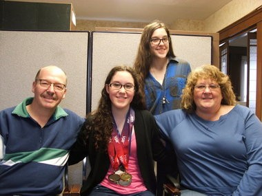 Lauryn DeLuca (wearing medals) poses with her father Steve (left) mother Tracy (right) and sister Olivya (standing). (Mark Holan/Special to Sun News)