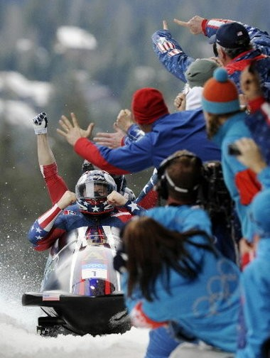 American bobsled fans try to share the celebration of the United States' USA-1, with Steven Holcomb, front, Justin Olsen, Steve Mesler, and Curtis Tomasevicz after the team won the 2010 Vancouver Olympics gold medal.