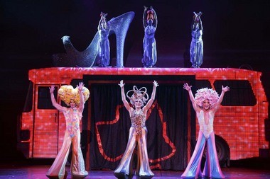 "Gumby goes glam. From left to right: Wade McCollum (as Tick/Mitzi), Scott Willis (as Bernadette) and Bryan West (as Adam/Felicia) in ""Priscilla Queen of the Desert,"" now playing at the State Theatre. On top of the bus, from left to right: Emily Afton, Brit West, Bre Jackson as the Divas."