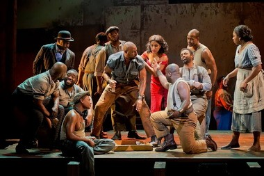 """The denizens of Catfish Row, with Alicia Hall Moran as Bess in red, play craps in """"The Gershwins' Porgy and Bess."""""""