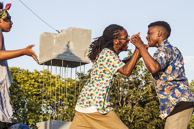 """From left: Kaundima Ashley and Elijah DeBerry perform in """"Road Trip,"""" a scene from """"And Yet, We Shine."""" The set, with its crumbling concrete pillar, was designed and built by STEP's 13-member tech team to evoke a post-apocalyptic world where freedom of expression is stifled."""
