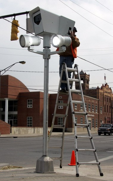 A worker from Redflex Traffic Systems Camera installs a traffic camera Thursday, March 2, 2006 in Columbus, Ohio. The former CEO of Redflex pleaded guilty in federal court Friday to bribing Columbus and Cincinnati officials to win or keep camera contracts.