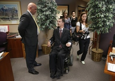 Attorney Michael Evans, left, talks with his client, Brandon Coats. On June 15, 2015, Colorado's Supreme Court ruled that Coats, a quadriplegic and medical marijuana patient who was fired by Dish Network after failing a drug test, cannot get his job back. (AP Photo/Brennan Linsley)
