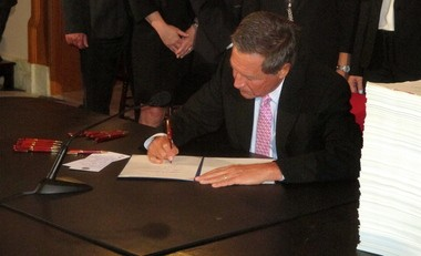 Gov. John Kasich signs the 2016-2017 state budget into law Tuesday during a ceremony in the Ohio Statehouse.