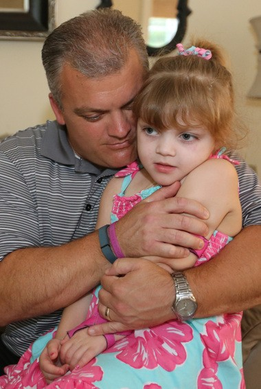 Paige Frate, 5, of Concord held by her father, Brian, at their Concord Township home. Brian and Kristina Frate doubt Issue 3 will produce enough medical marijuana to help their daughter and other families like theirs.