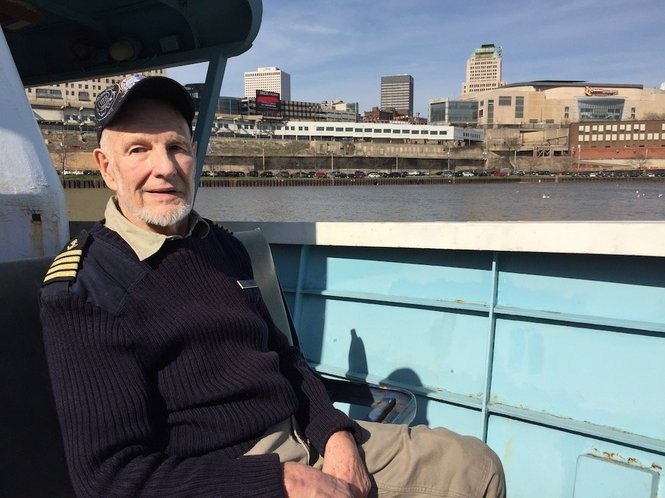 WayneBratton, the 82-year-old owner of Trident Marine Corp., sits in his company's boat in the Cuyahoga River.
