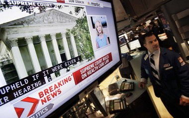 A television screen on the floor of the New York Stock Exchange headlines the 2012 Supreme Court ruling on the Affordable Care Act, which hospitals say is now affecting their revenues.