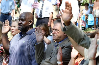Danton Patterson, left, from Jamaica, and Michael Haddad, center, from Lebanon, raise their hands with other immigrants taking the oath of allegiance to the United States during the naturalization ceremony at the One World Festival at the Cleveland Cultural Gardens' Irish garden on Aug. 26.