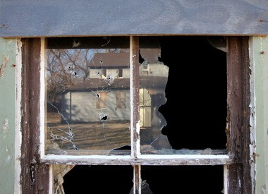 A broken and gunshot window on a condemned home on Avery Avenue in Cleveland, photographed in February 2012, reflects another condemned home behind it.