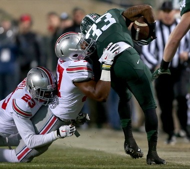 Buckeyes linebacker Joshua Perry (37) and safety Tyvis Powell (23) combine to tackle Michigan State Spartans running back Jeremy Langford (33). Perry leads the team in tackles with 118.