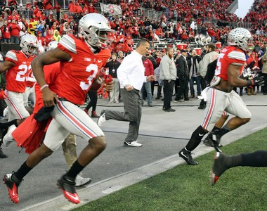 Ohio State running back Ezekiel Elliott, right, jogs onto the field with extra padding on his right shin. He spent time in the hospital earlier in the week and wasn't sure if he was going to play.