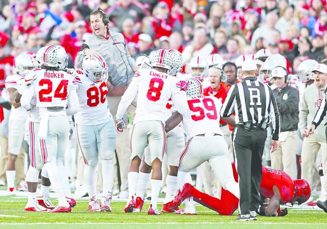 Luke Fickell (in air) celebrated a fourth-down stop against Maryland with the defense this season.