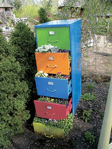A recycled file cabinet can be used as a whimsical plant container in a garden.