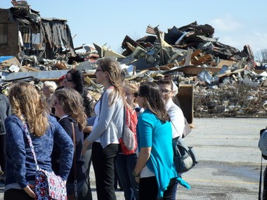 As students and administrators watched the groundbreaking ceremony, work on demolition of the old O'Brien Athletic Center, to the rear, was temporarily halted.