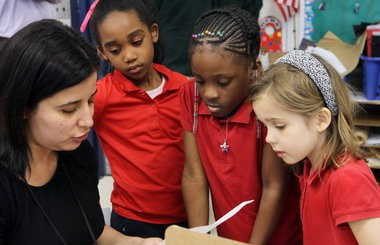 Iliam Cortez works with some of her pupils at the Near West Intergenerational School, a part of the Breakthrough group of charter schools in Cleveland. Breakthroughs' schools, like charter schools across Ohio, are waiting to see details of their funding under the proposed education budget.