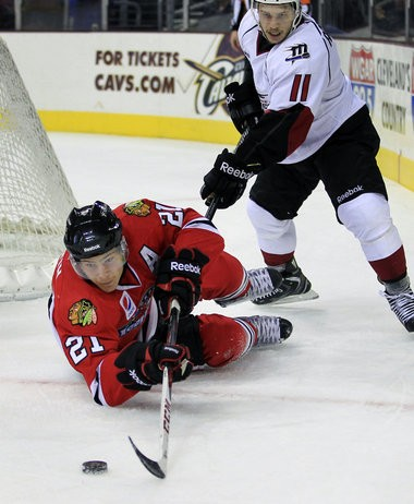 Lake Erie Monsters left winger Andrew Agozzino, right, defends fallen Rockford Icehogs winger Ben Smith, who had fallen while playing the puck in the first period, Nov. 23.