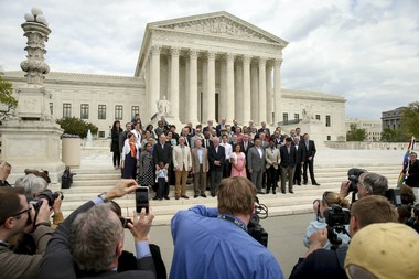 Plaintiffs from Tennessee, Michigan, Kentucky and Ohio pose for photographs with the lawyers representing them in front of the Supreme Court in Washington, Monday, April 27, 2015, as the Supreme Court is scheduled to hear arguments on the constitutionality of state bans on same-sex marriage on Tuesday.