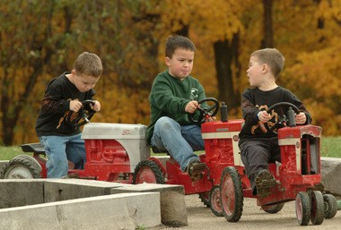 Michael French, 4, yells to his older brother Matthew, 7, to stop pushing as his twin brother Danny waits to start moving at the peddle tractor track at the Patterson Family Fun Fest in this 2004 photo.