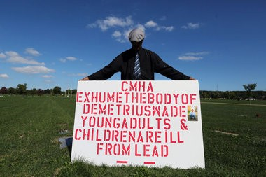 """At Cleveland Memorial Gardens, where his son, Demetrius, is buried, Darrick Wade holds a sign to protest Cuyahoga Metropolitan Housing Authority's treatment of lead in housing properties. Though it's impossible to directly link Demetrius's death to his lead exposure, he suffered from a number of diseases that have been linked to the toxin, including chronic kidney disease and heart disease. """"For him to die so young is just a shame,"""" said Darrick Wade. """"For nobody to care it is still happening is even worse."""""""