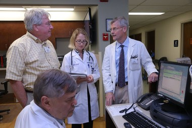 Dr. Ted Parran, far right, talks to addiction medicine to fellows and Physician Assistant Michael Grodach at St. Vincent Charity Medical Center. Parran says all forms of Medication Assisted Treatment can help with recovery when paired with treatment.