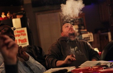 The Rev. Rob Plain of Mt. Calvary Evangelical Lutheran Church in Cleveland exhales a puff of cigar smoke during a twice-a-month Bible study in the backroom of Cigar Cigars, a smoke shop in Rocky River.