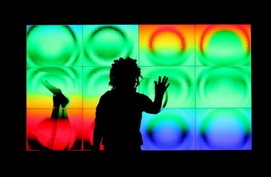 """Tashara Deaver, 7, of Cleveland Heights, stands in front of an interactive screen and paints at the """"Lines Play"""" station inside the new Gallery One at the Cleveland Museum of Art."""