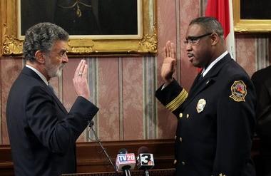 Cleveland Mayor Frank Jackson, left, swears in new fire chief Daryl McGinnis.