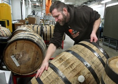 Andrew Markelonis, distiller for Cleveland Whiskey, arranges white-oak barrels for storage in the company's distillery on Friday, the first day the new bourbon went on sale.