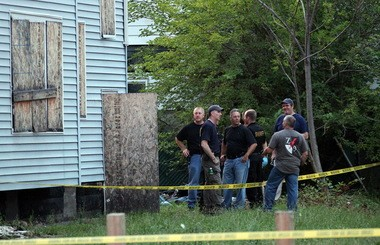 Police and FBI agents at the boarded-up home where bodies were found Saturday at Shaw and Hayden avenues in East Cleveland.