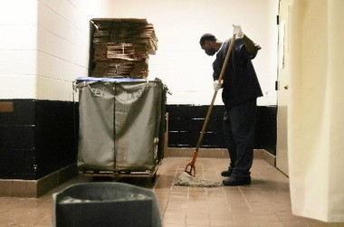An inmate at the Lorain Correctional Institution mops the floor in a processing area where inmates have their hair cut.