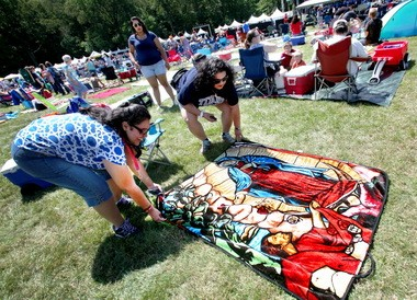 Milly Pulliam, left, and Anna Parrilla, both of Lorain, spread Pulliam's blanket in front of the music stage at the FEST, the 13th annual Catholic festival and celebration. Pulliam recieved th religious-themed blanket as a Christmas present. The women are members of Sacred Heart Church in Lorain.