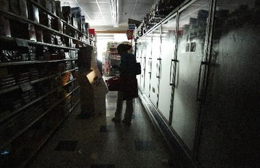 NEW YORK -- Aug. 15, 2003. A woman uses a flashlight while looking for non-perishable groceries in a darkened store in Manhattan's Upper East Side. (Ruth Fremson/The New York Times)