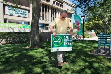 Gerry Modjeski, director of employee benefits and wellness at Cleveland State University, installs a sign indicating the campus is tobacco-free.