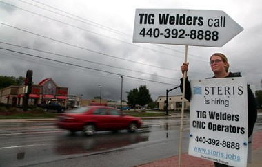 Steris Corp. in Mentor is so desperate to find skilled workers that is taking its message to the streets. Here sign holder Kelsey Flugenzi braves the rain along Mentor Avenue to help get the word out.