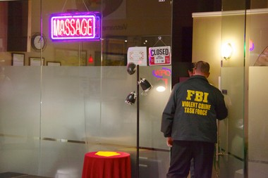 An FBI agent enters the Relax Zone massage parlor on Cleveland's East Side during the execution of a search warrant Nov. 6, 2013.