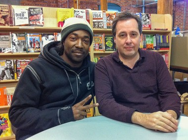 Reluctant hero Charles Ramsey, left, and writer Randy Nyerges at the contract-signing for a memoir about Ramsey's life before and after the famous rescue on Seymour Avenue.