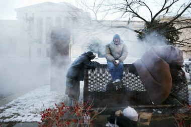 Four homeless men warm themselves on a steam grate by the Federal Trade Commission, blocks from the U.S. Capitol, in Washington on Saturday as the winter storm that swept across the Midwest reached the East Coast.