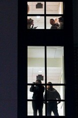 Kent State students gather around windows in Stopher residence hall overlooking portions of the campus that were still locked down Wednesday because of a gunshot.