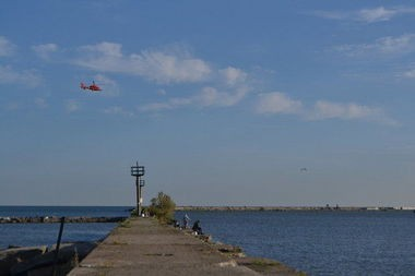 A Coast Guard helicopter hums along the Lake Erie in Cleveland Monday as crews search for a missing swimmer from New York.