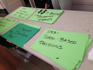 The Cleveland school district handed out signs to administrators that support the district's new budgeting plan as a counter to the protests from teachers at Thursday's school board meeting.